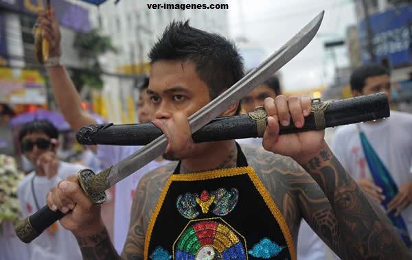Se atraviesan palos y espadas en sus mejillas por fiesta budista