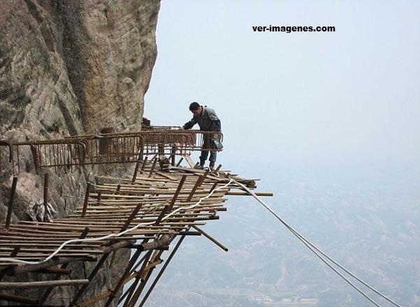 Trabajadores chinos hacen un sendero alrededor de un acantilado