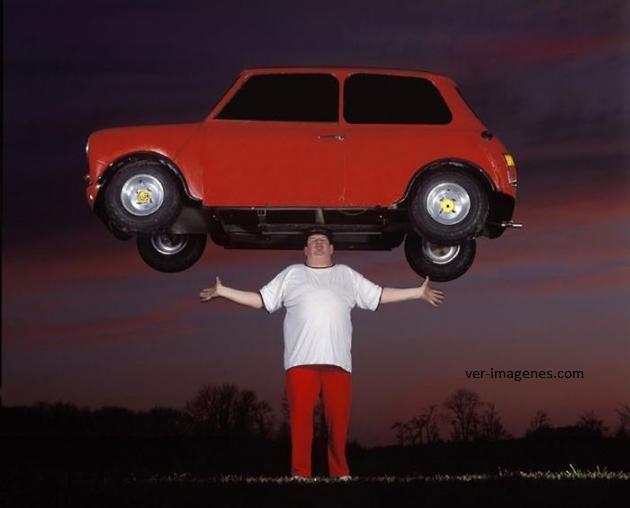 Sosteniendo un auto pequeño sobre su cabeza