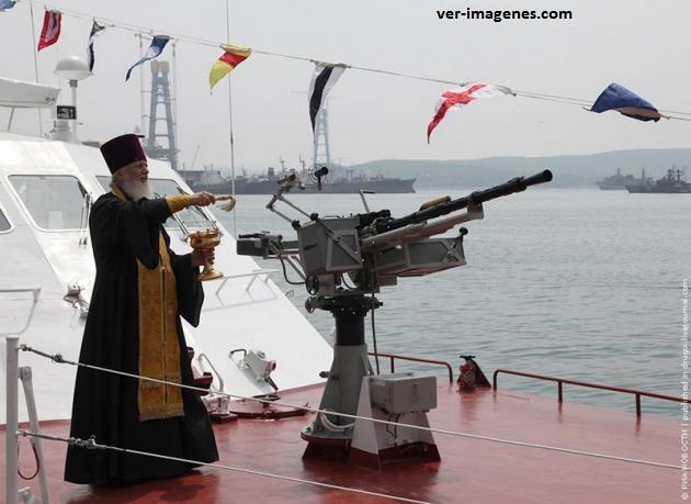 Sacerdote bendiciendo una ametralladora en un buque
